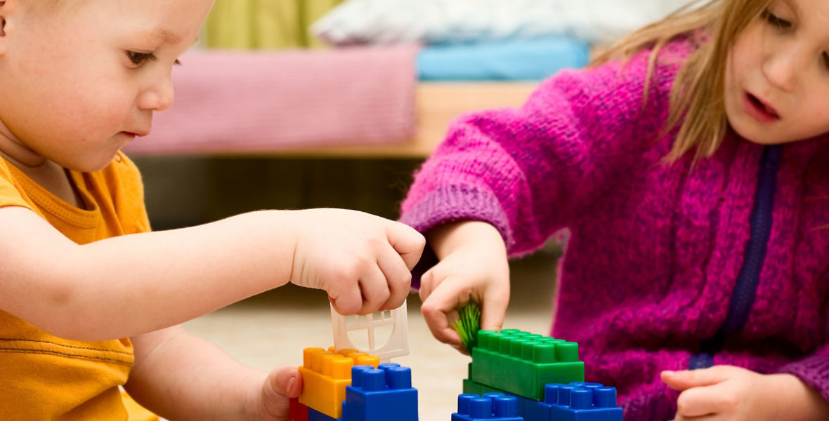 Två barn bygger hus av plastklossar