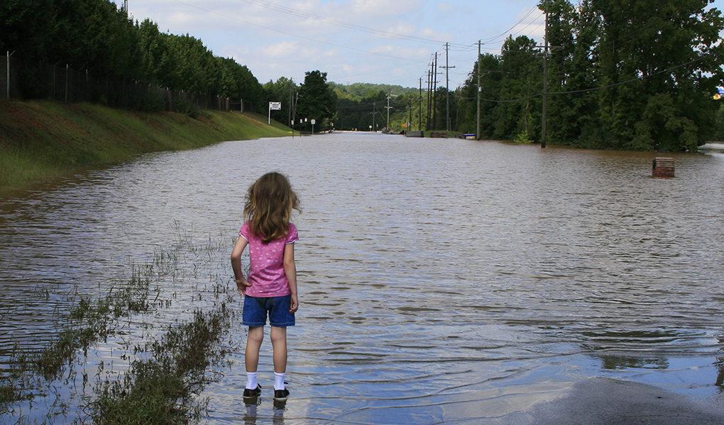 Flicka på översvämmad väg